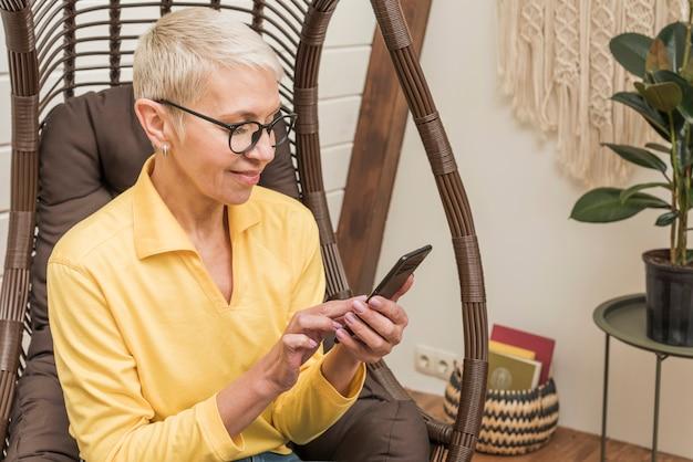 Mooie senior vrouw met behulp van haar telefoon