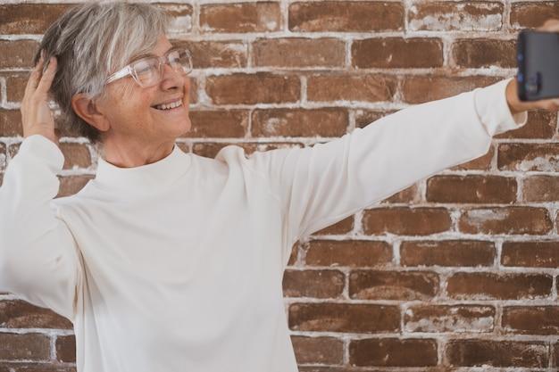 Mooie senior vrouw met behulp van telefoon staande tegen een bakstenen muur glimlachend