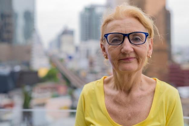 Mooie senior vrouw met bril in de stad