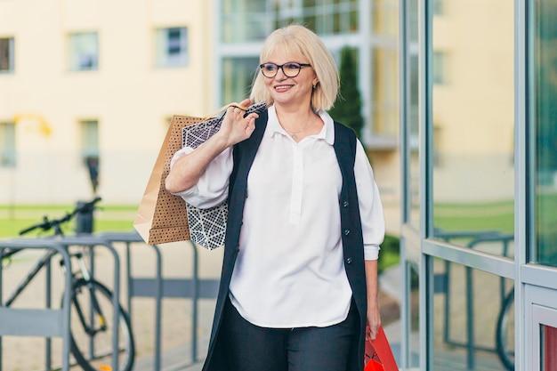 Mooie senior vrouw met gekleurde zakken voor goederen en geschenken op de achtergrond van de supermarkt