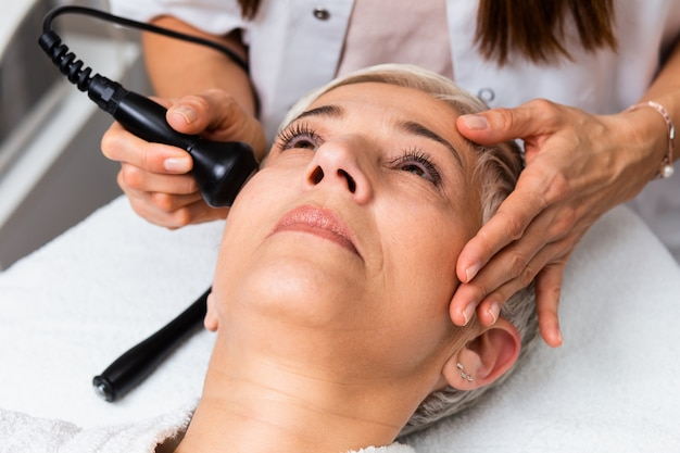 Mooie senior vrouw met mesotherapie bij cosmetische schoonheidssalon.