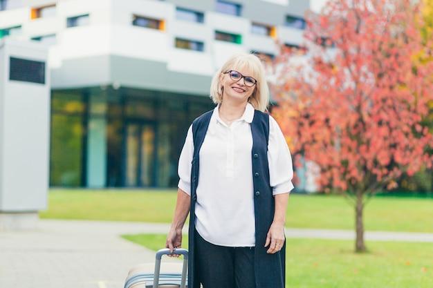 Mooie senior vrouw reist met een grote reiskoffer, op de achtergrond van een prachtig modern gebouw