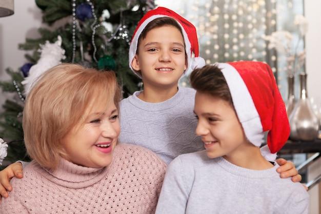 Mooie senior vrouw viert kerstmis met haar kleinzonen