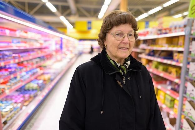 Mooie senior vrouw winkelen bij de supermarkt