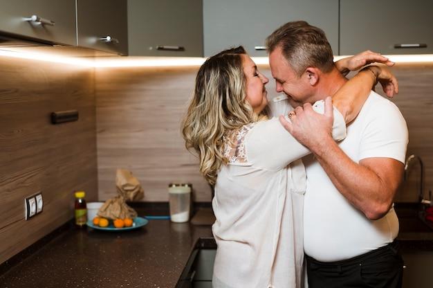 Mooie senioren knuffelen in de keuken