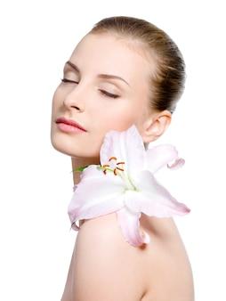 Mooie sensualiteit jonge vrouw met bloem op een schouder met gesloten geïsoleerde ogen -