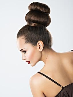 Mooie sensuele vrouw met creatief kapsel. vrij jong volwassen meisje met bruine oogmake-up en rode lippen