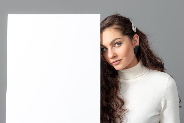Mooie sensuele zakenvrouw met lang krullend haar toont een blanco bilboard, geïsoleerd op grijs, kopieer ruimte
