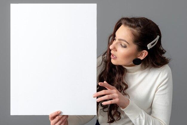 Mooie sensuele zakenvrouw met lang krullend haar toont een leeg bord