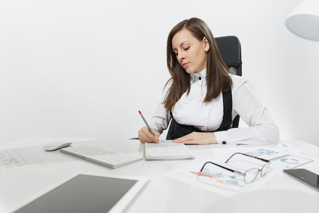 Mooie serieuze bruinharige zakenvrouw in pak en bril zitten aan de balie, werken op de computer met moderne monitor en documenten in licht kantoor, schrijven in notitieblok