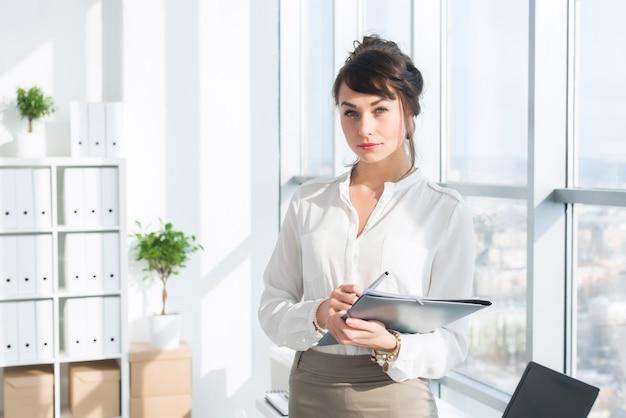 Mooie, serieuze consultant die een bril en een formeel kantoorpak draagt, haar werk stationair houdt,