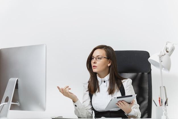 Mooie serieuze verdiepte bruinharige zakenvrouw in pak en bril zittend aan het bureau, werkend op computer met moderne monitor met documenten en tablet in licht kantoor