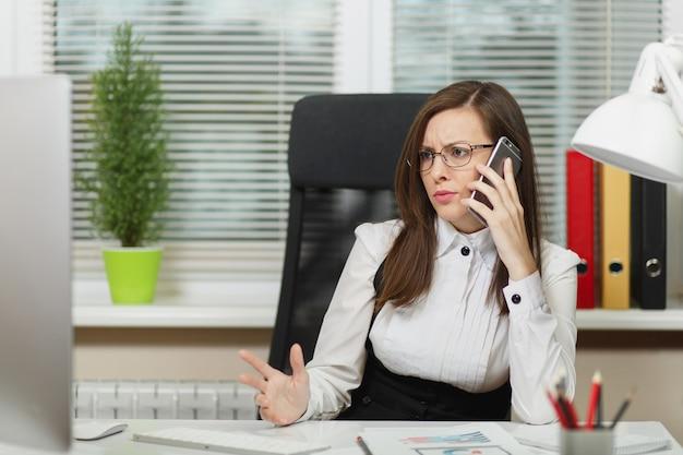 Mooie serieuze zakenvrouw in pak en bril die aan het bureau zit, werkt op een moderne computer met documenten in een licht kantoor, praat op een mobiele telefoon die problemen oplost, opzij kijkt