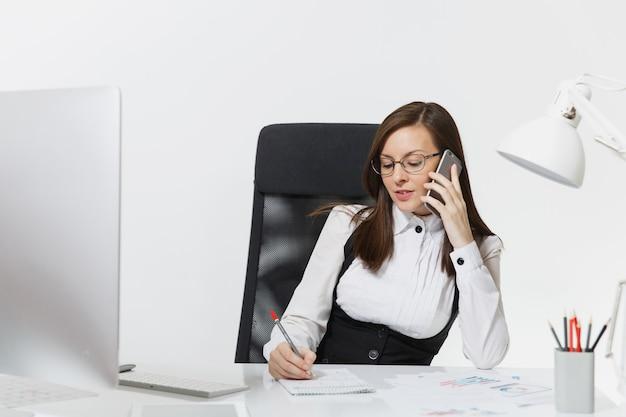 Mooie serieuze zakenvrouw in pak en bril die aan het bureau zit, werkt op een moderne computer met documenten in een licht kantoor, praat op een mobiele telefoon om problemen op te lossen,