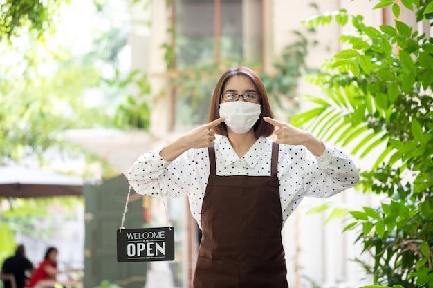 Mooie serveerster bedrijf bordje met de tekst 'welkom, we zijn open' in de koffiewinkel of de restaurantdeur