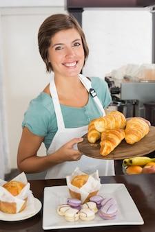 Mooie serveerster die dienblad van croissants toont