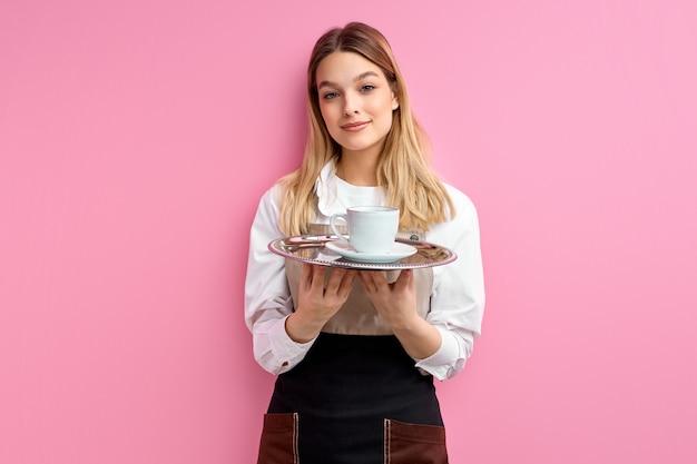 Mooie serveerster die kop van koffie aanbiedt die op roze muur wordt geïsoleerd