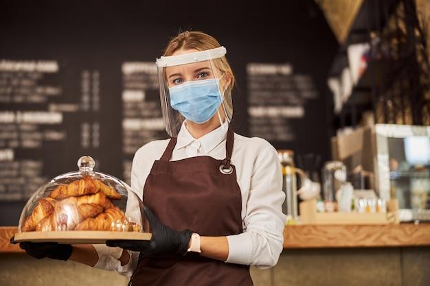 Mooie serveerster met een dienblad met gebak in café tijdens pandemie