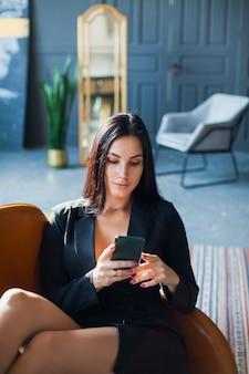Mooie sexy blogger die smartphone thuis gebruiken.