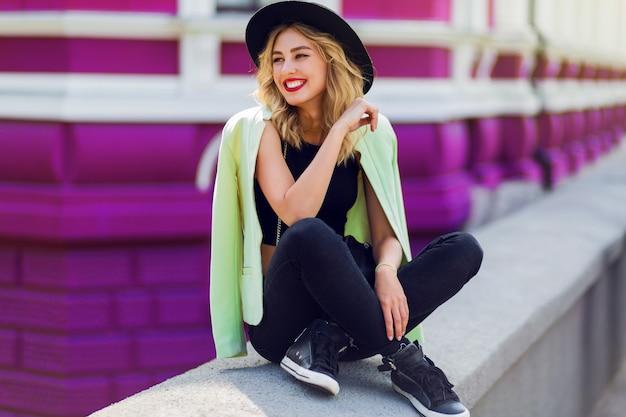 Mooie sexy blonde meisje in casual kleding met perfecte figuur wandelen door de stad. mode en stadsstijl. zwarte stijlvolle hoed, korte top. sensuele volle lippen.