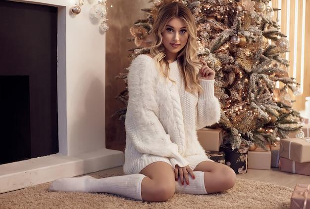 Mooie sexy blonde vrouw die in witte sweater dichtbij kerstmisboom glimlacht