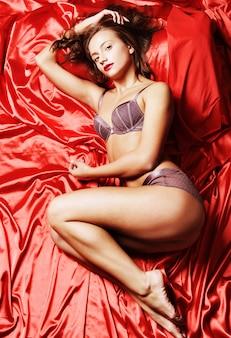 Mooie sexy bochtige jonge vrouw in lingerie die in bed ligt.