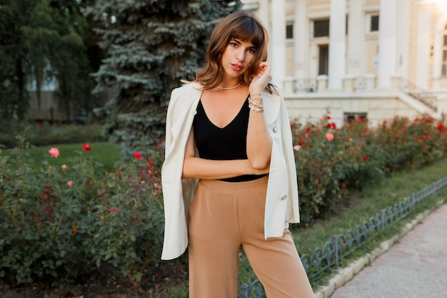 Mooie sexy brunette meisje in casual kleding met perfecte figuur wandelen rond het stadscentrum. elegante stijl. witte jas.