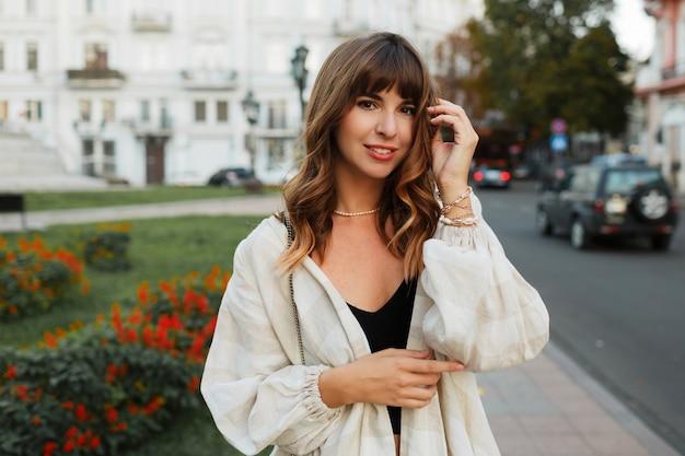 Mooie sexy brunette meisje in casual kleding met perfecte figuur wandelen rond het stadscentrum. elegante stijl.