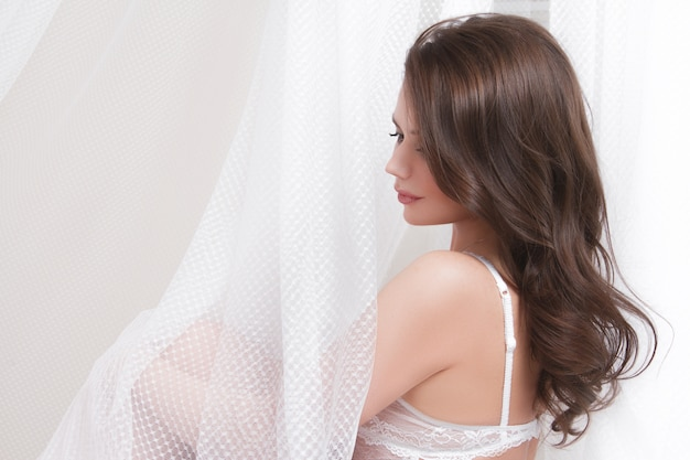 Mooie sexy brunette met grote borsten zit op het bed