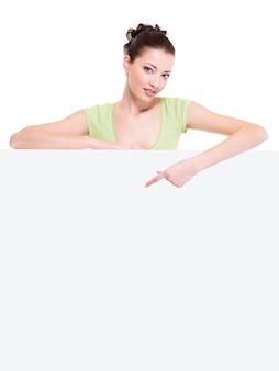 Mooie sexy cuacasian vrouw onder de witte lege banner wijst door wijsvinger erop