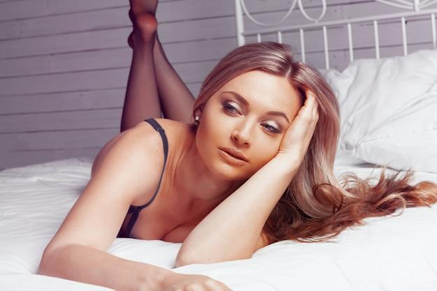 Mooie sexy dame in elegant zwart slipje en kousen in bed
