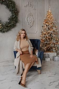 Mooie sexy jonge blonde vrouw in stijlvolle kleding zittend in een fauteuil in de buurt van de kerstboom...