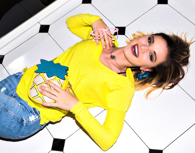 Mooie sexy jonge vrouw die op witte vloer legt. het dragen van een kleurrijk zomeroverhemd met grappige ananaszak. lifestyle foto van vrolijke vrouw