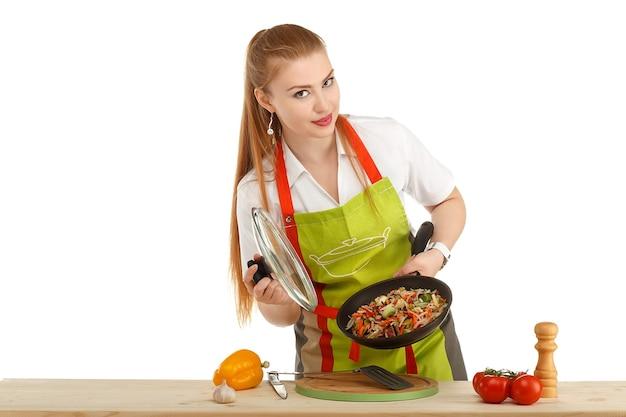 Mooie sexy jonge vrouw die verse die maaltijd kookt die op wit wordt geïsoleerd
