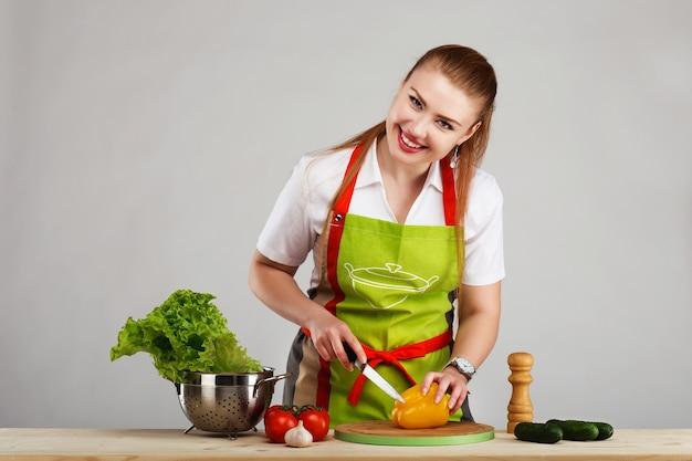 Mooie sexy jonge vrouw die verse maaltijd kookt tegen grijs
