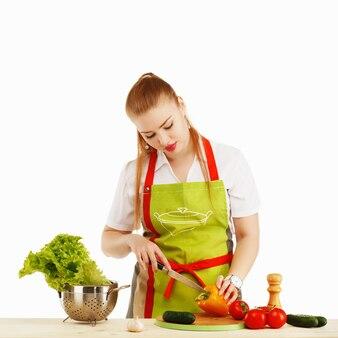 Mooie sexy jonge vrouw die verse maaltijd tegen wit kookt.