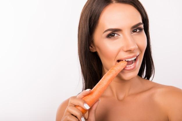 Mooie sexy jonge vrouw die wortel eet