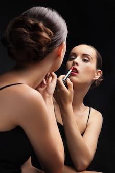 Mooie sexy jonge vrouw houdt lippenstift in de buurt van een spiegel op zwarte achtergrond