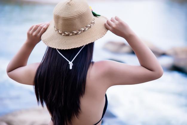 Mooie sexy jonge vrouw in bikini bij rots van waterval