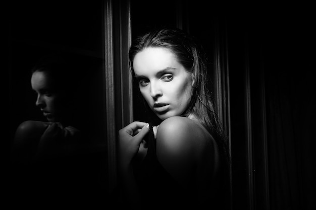 Mooie sexy jonge vrouw in de buurt van een glas op zwarte achtergrond
