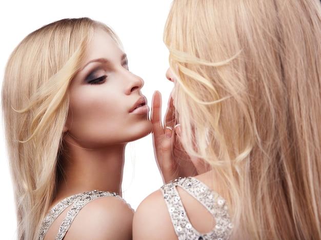 Mooie sexy jonge vrouw in de buurt van een spiegel op witte achtergrond