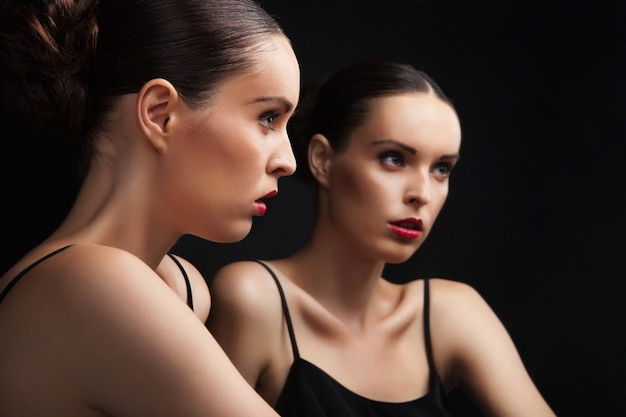 Mooie sexy jonge vrouw in de buurt van een spiegel op zwarte achtergrond