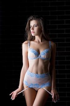 Mooie sexy jonge vrouw in lingerie die zich op muurachtergrond bevindt