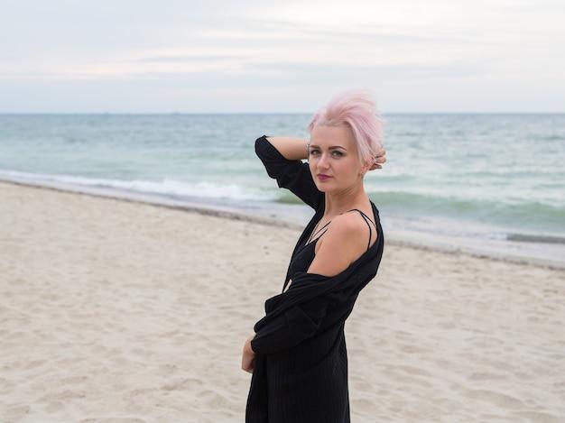 Mooie sexy jonge vrouw met roze haren trendy kapsel en sensuele look hipster punk meisje in zwart vest poseren aan de oever van de oostzee