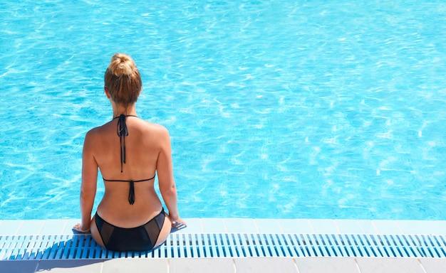 Mooie sexy jonge vrouw zittend op de rand van het zwembad.