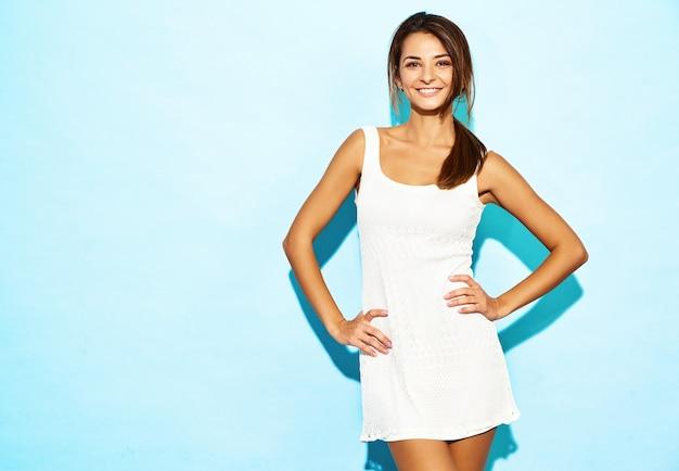 Mooie sexy jonge zakenvrouw met donkerbruin haar en natuurlijke make-up. vrouw draagt witte jurk. model poseren op blauwe muur