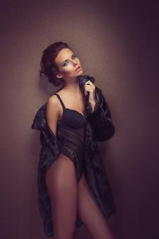 Mooie sexy langharige brunette vrouw in zwarte lingerie en bontjas poseren