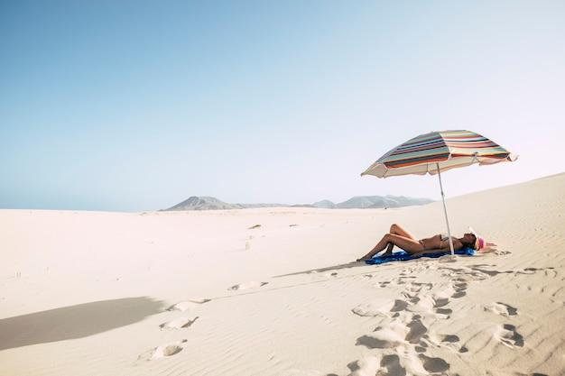 Mooie sexy lichaam vrouw leggen en rusten op het strand als een woestijnduinen met zon over haar zonnebaden en gebruinde huid voor concept vakantie zomer vakantie alleen op het strand genieten van levensstijl