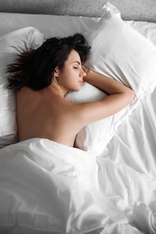 Mooie sexy meisje slapen op een kussen onder een witte deken op het bed
