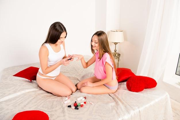Mooie sexy meisjes in pyjama nagels lakken met vernis